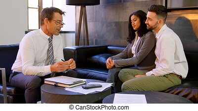 Couple discussing with broker on sofa 4k