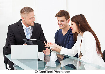 Couple Discussing With Financial Advisor - Smiling young...