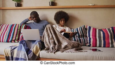 couple, divan, séance, lecture, utilisation ordinateur