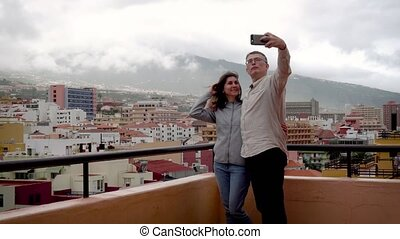 couple doing a selfie at phone on roof of house