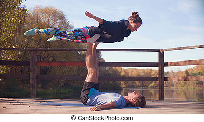 Couple doing acrobatic exercises on the bridge in the park