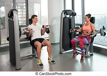 Couple Doing Exercise For Biceps In Gym