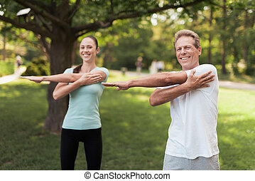 Man and woman doing exercises in the park. They warm up