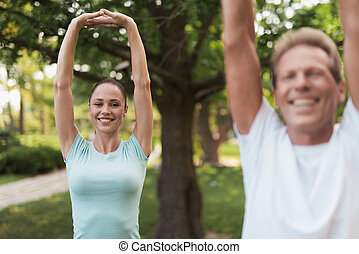 Couple doing exercises in the park. They do stretching hands