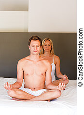 Couple doing exercises on bed with copy-space