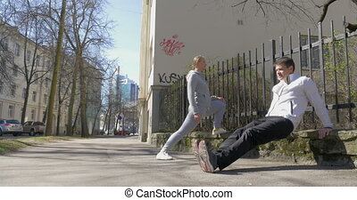 Couple doing morning exercises in city street
