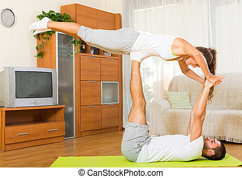 Young couple enjoying regular exercises together at home