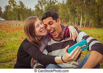 Couple doing silly and funny faces while taking selfie picture with their mobile phone in field of red poppies