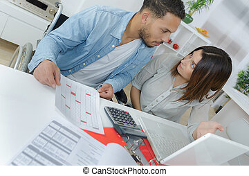 couple doing their accounts with spreadsheets and laptop