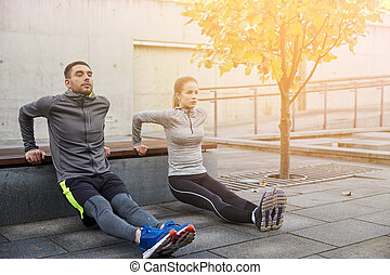 couple doing triceps dip on city street bench - fitness,...