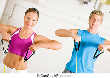 Couple doing Tube Training in gym