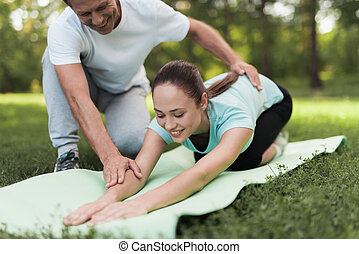 Woman doing warm-up on a rug for yoga, a man helping her