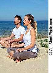 Couple doing yoga exercises on a sandy beach