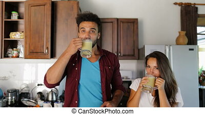 Couple Drink Fresh Smoothie Talking Man And Woman In Kitchen Together Happy Smiling