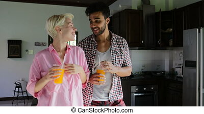 Couple Drink Orange Juice Dance In Kitchen, Young Happy Man And Woman Morning Communication In Modern Apartment