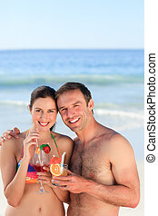 Couple drinking a cocktail on the beach