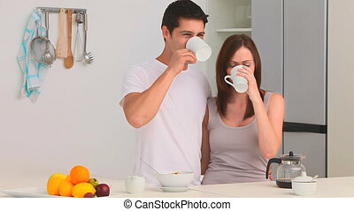 Couple drinking a cup of coffee in the kitchen at home