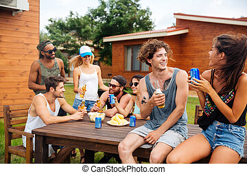 Couple drinking beer and soda with friends on outdoor party