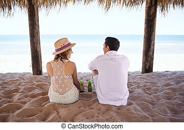 Couple drinking beer at the beach