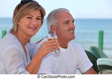 Couple drinking beer in beach terrace