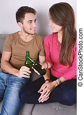 Couple drinking beer on couch.