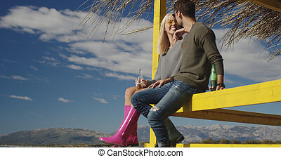 Couple drinking beer together at the beach