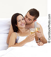 Couple drinking champagne in bed in valentine\'s day - Happy...