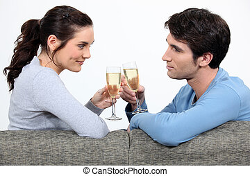 Couple drinking champagne on sofa