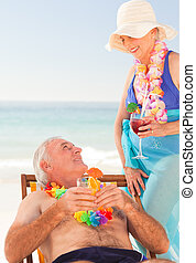 Couple drinking cocktails at the beach