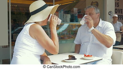 Couple drinking coffee and taking selfie on smartphone