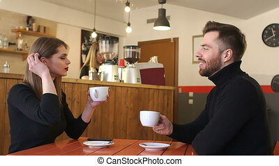 Couple drinking coffee on a first date in a coffee shop. Slow motion.