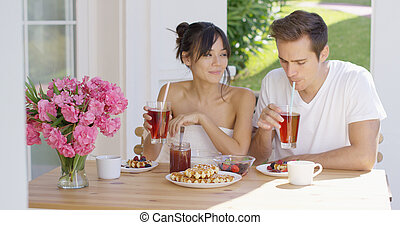Couple drinking iced tea at breakfast outside - Young...