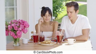 Couple drinking iced tea at breakfast outside