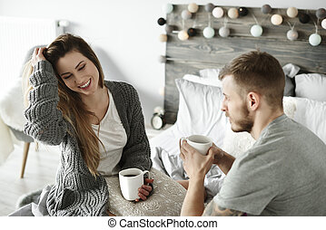 Couple drinking morning coffee at bedroom