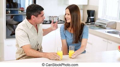 Couple drinking orange juice and chatting