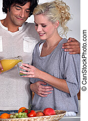 Couple drinking orange juice in the kitchen