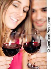 Couple drinking red wine clinking glasses - Young couple -...