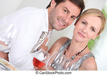 Couple drinking rose wine at a dinner party
