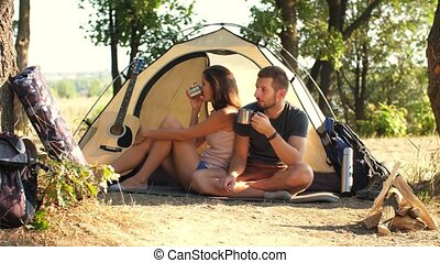 Couple drinking tea at campsite tent - Happy couple drinking...