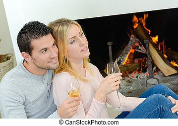 Couple drinking wine in front of an open fire