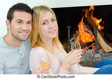 couple drinking wine in front of fire