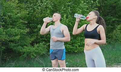 Couple drinks water from a bottle