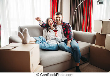 Couple drinks wine and celebrate moving to house