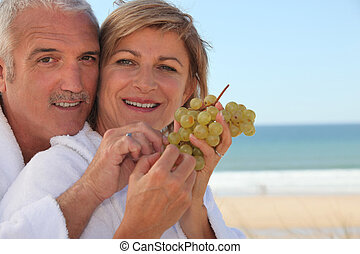 Couple eating a bunch of grapes