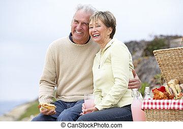 Couple Eating An Al Fresco Meal At The Beach