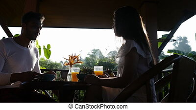 Couple Eating Breakfast On Summer Terrace, Man And Woman Communication While Enjoying Healthy Meal Outdoors In Morning