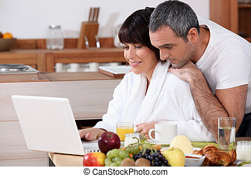 Couple eating breakfast together whilst browsing the...
