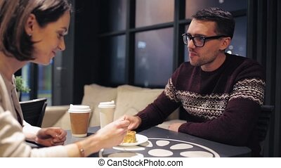 couple eating cake and drinking coffee at cafe