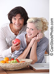 Couple eating fruit from basket in kitchen