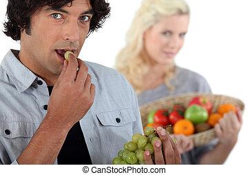 Couple eating fruit.